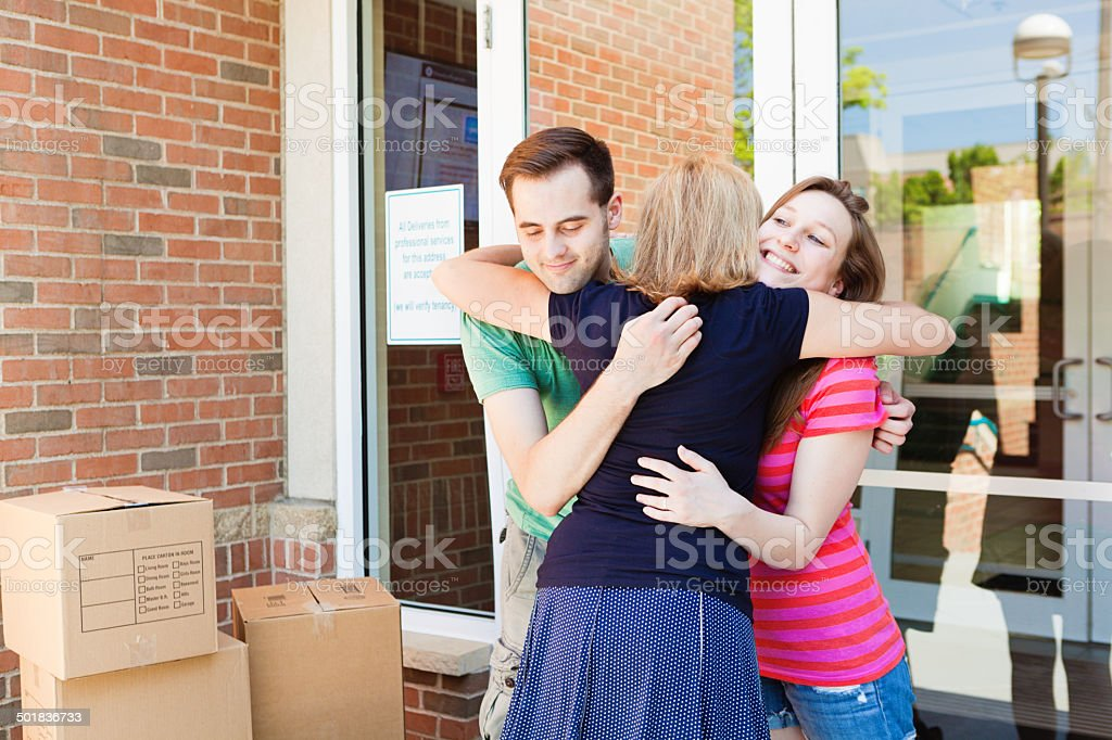 Parent Saying Goodbye to Students Moving into University Dormitory Vertical stock photo