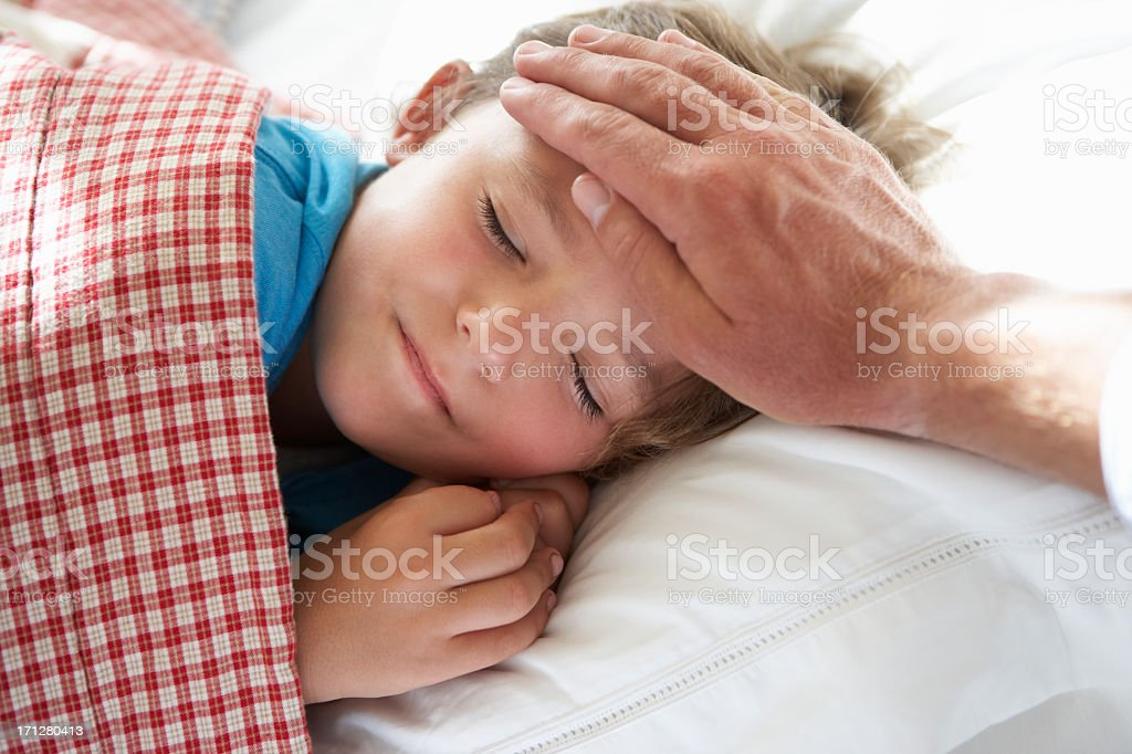 Parent Taking Temperature Of Young Boy Asleep In Bed royalty-free stock photo