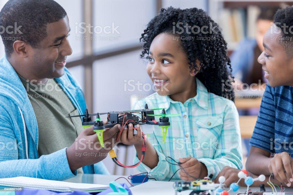 Parent volunteer helps students in after school engineering club stock photo