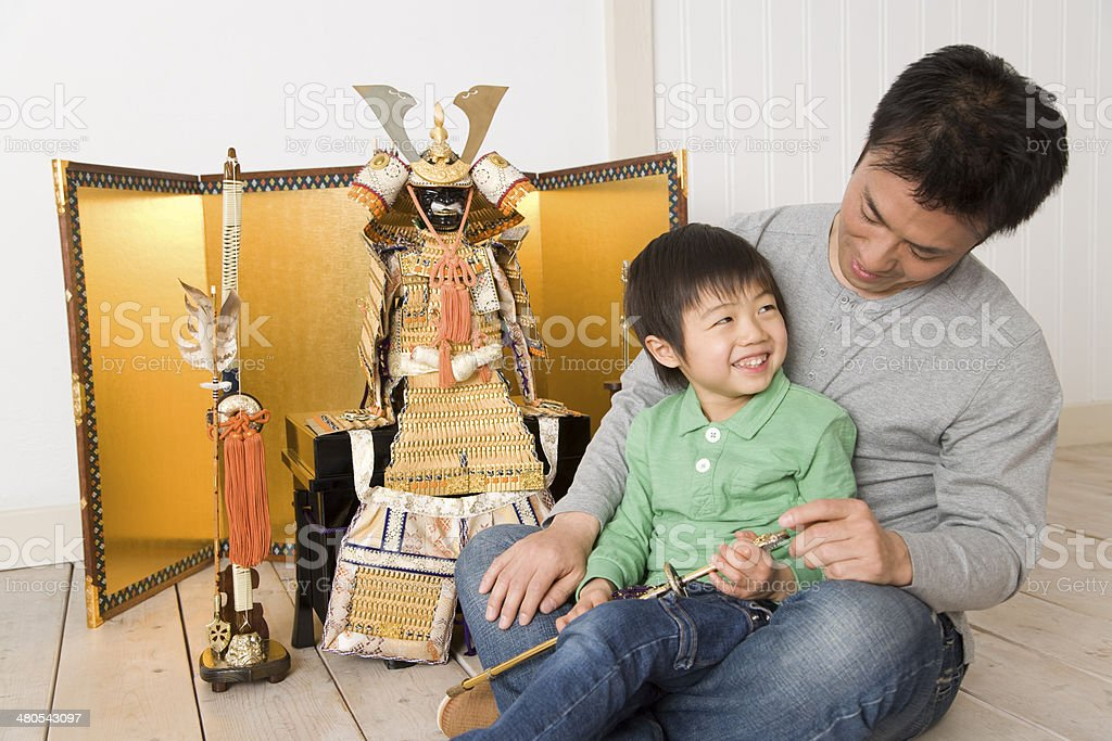 Parents and child sitting in front of May doll stock photo