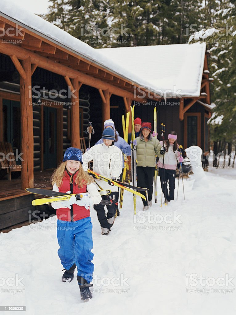 Parents and children (7-16) carrying cross-country skis beside c stock photo