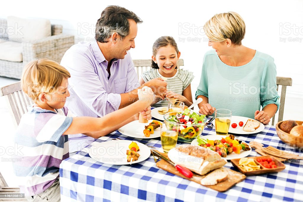 Parents And Children Enjoying Meal Outdoors royalty-free stock photo