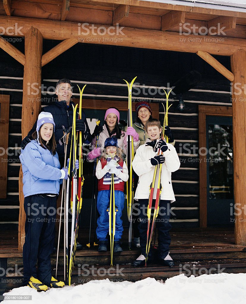 Parents and children (7-16) holding cross-country skis on porch stock photo