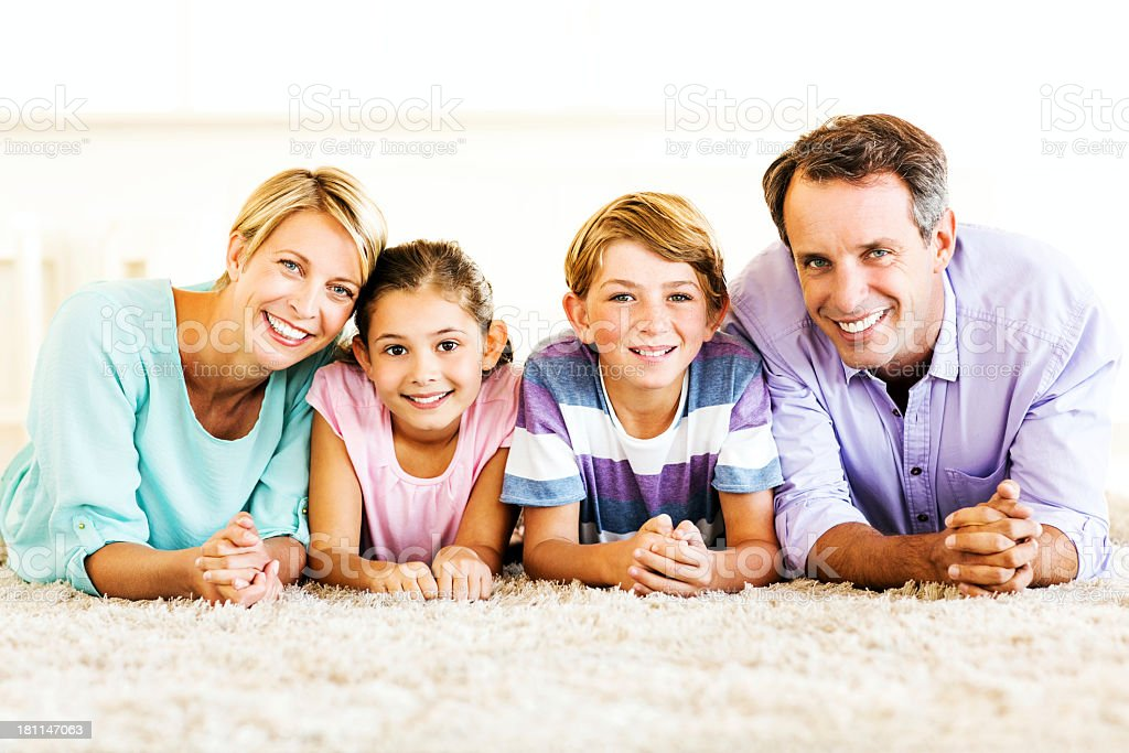 Parents And Children Lying On Carpet At Home royalty-free stock photo