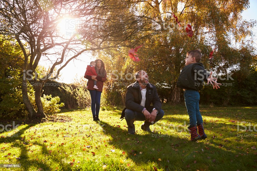 Parents And Children Playing With Autumn Leaves in Garden stock photo