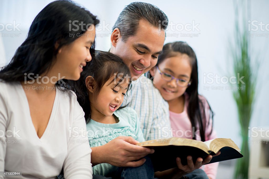 Parents and Children Studying Bible stock photo