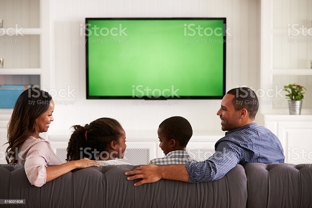 Parents and children watching TV, looking at each other stock photo