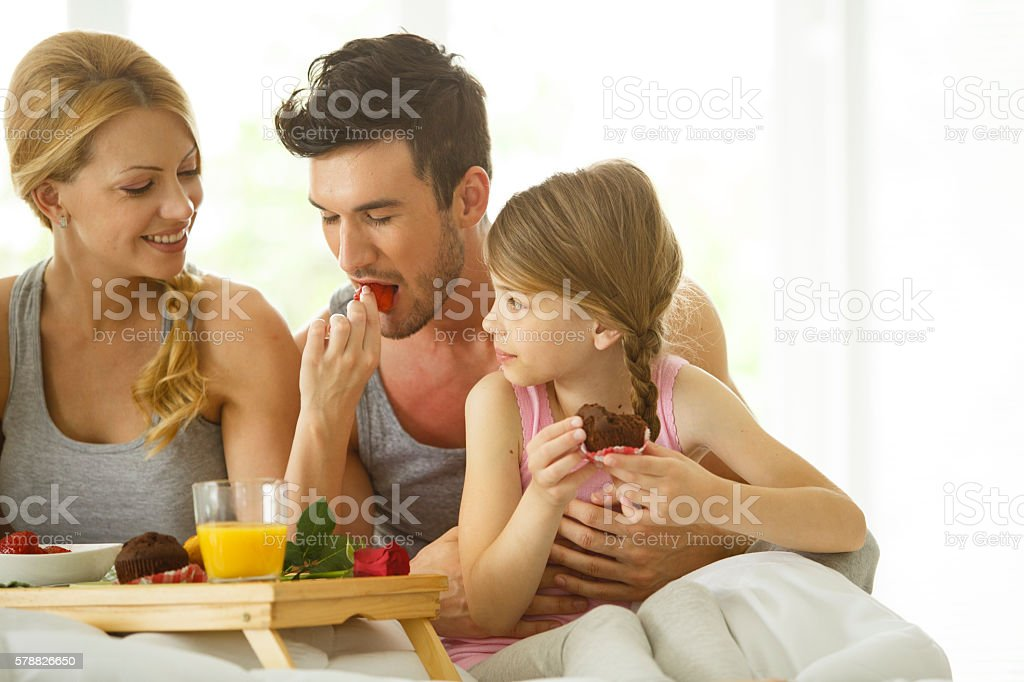 Parents and daughter having breakfast in bed stock photo