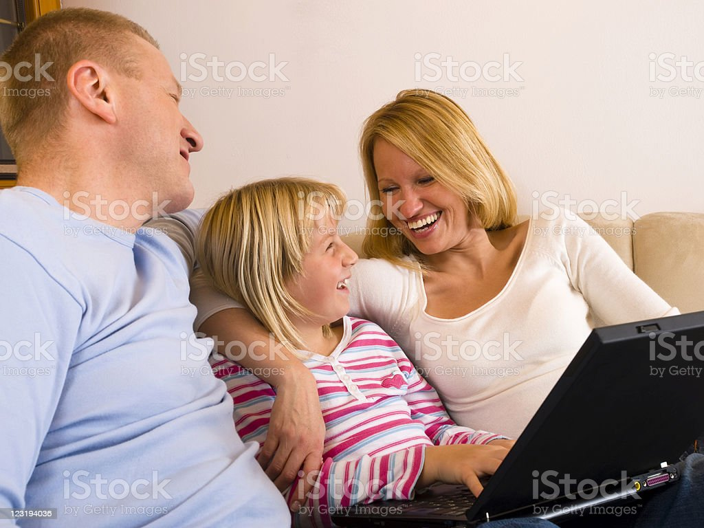 Parents and Daughter Using Laptop stock photo