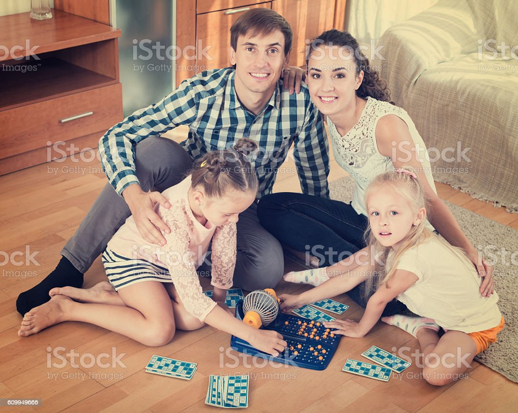 Parents and daughters with toy lotto stock photo