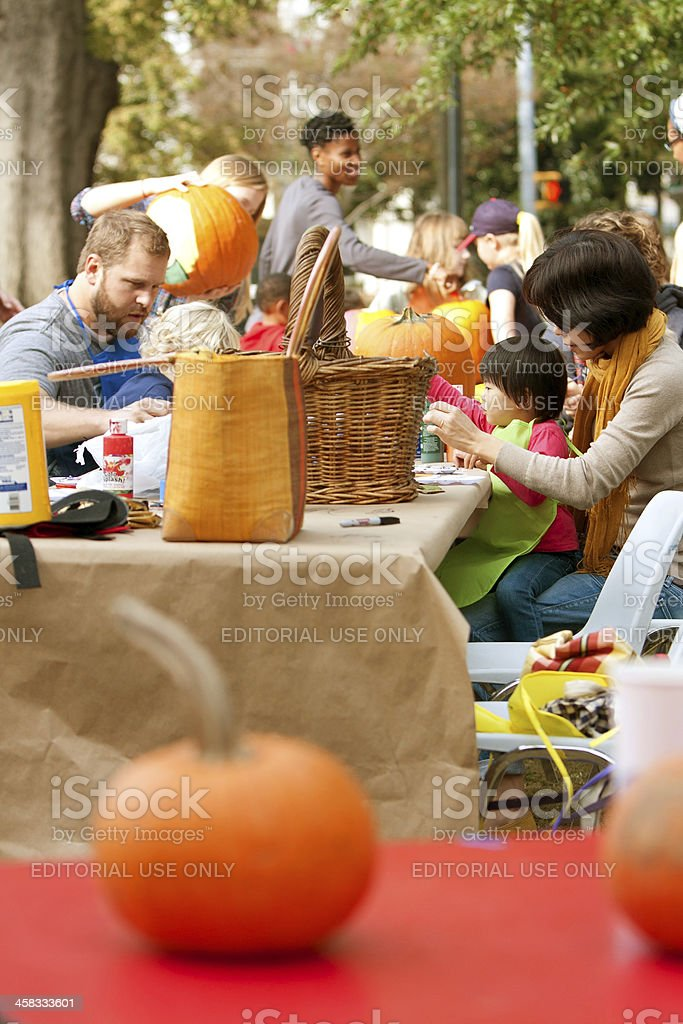 Parents And Kids Carve Pumpkins In A Public Park royalty-free stock photo