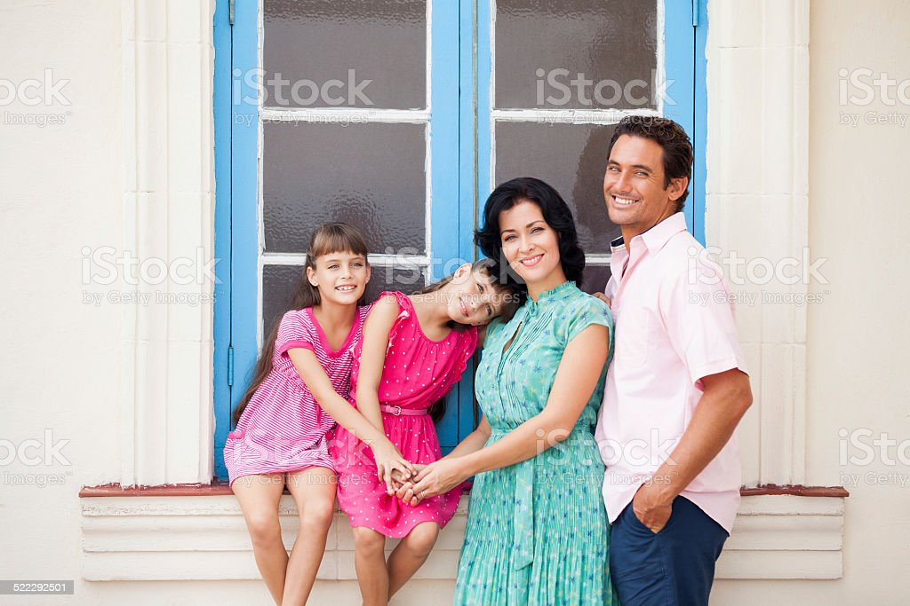 Parents and kids pose together next to window stock photo