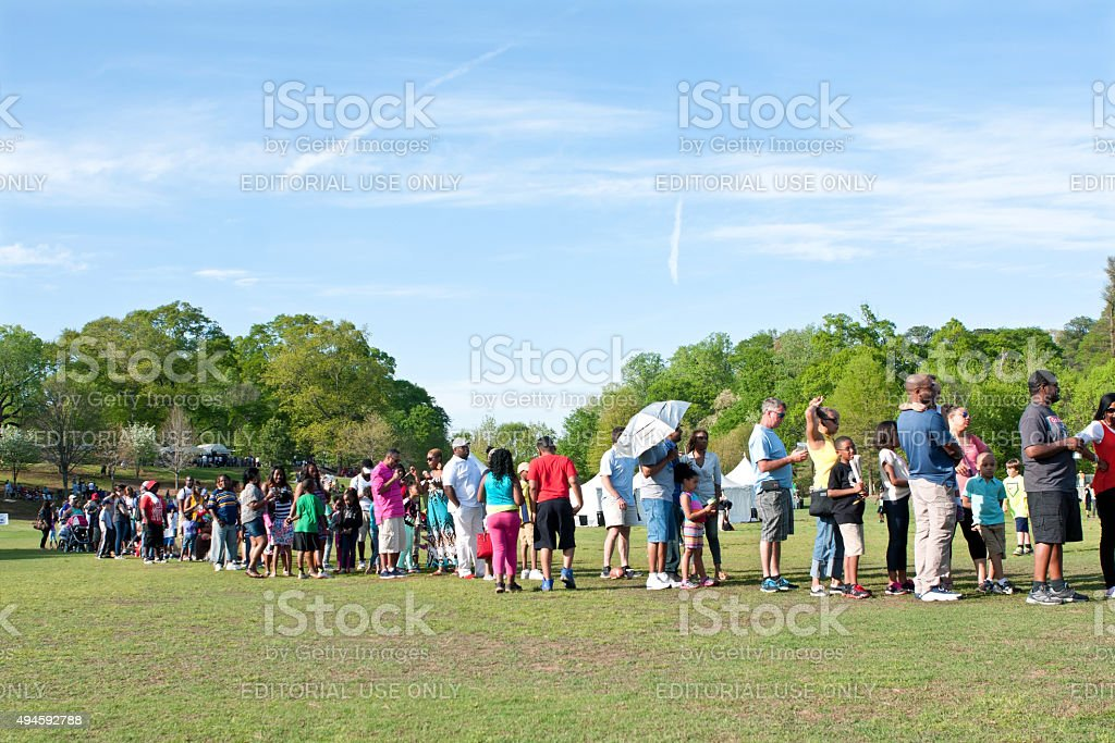 Parents And Kids Wait In Long Line For Festival Ride stock photo