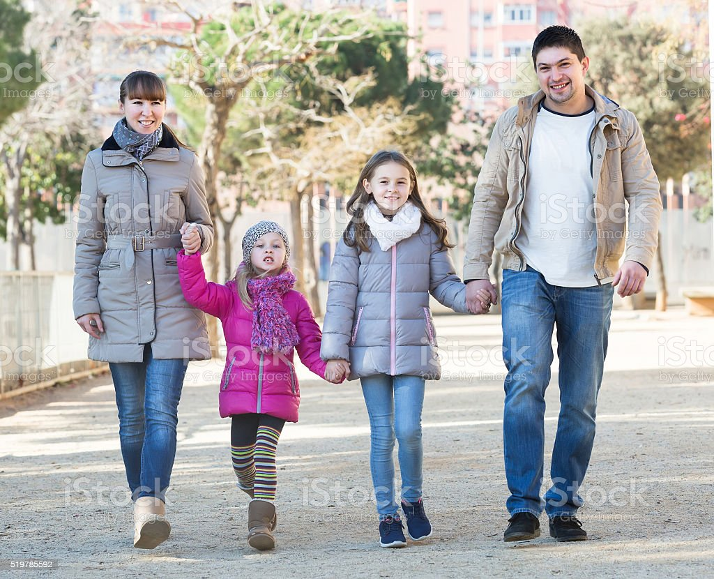 parents and little daughters taking a walk in park stock photo