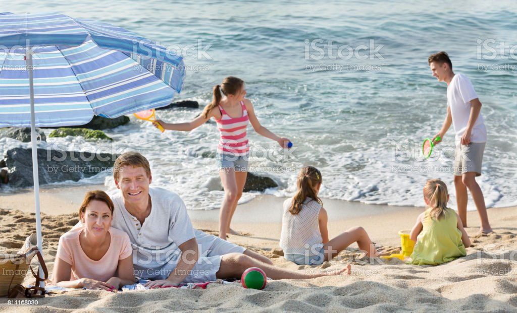Parents and playing children on beach stock photo