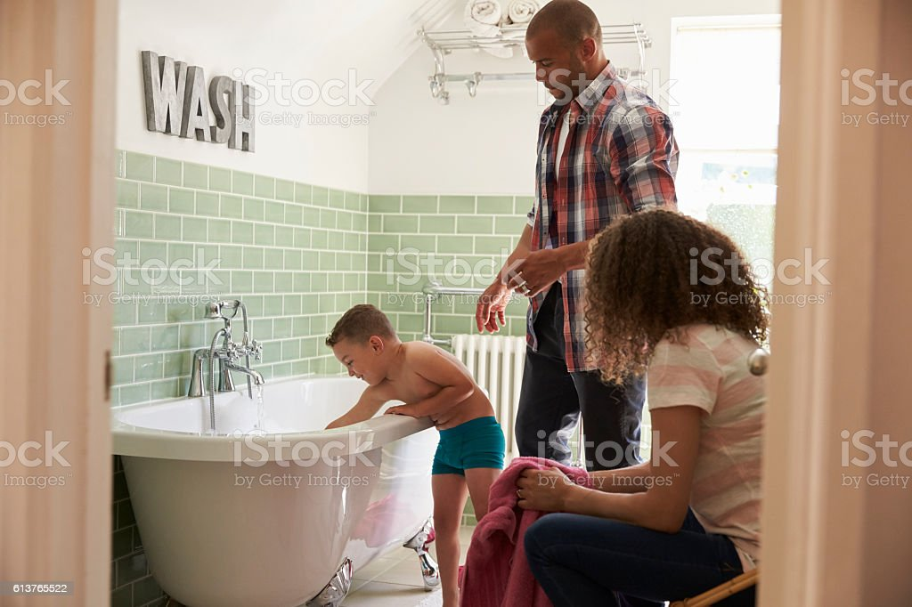 Parents And Son Having Fun At Bath Time Together stock photo