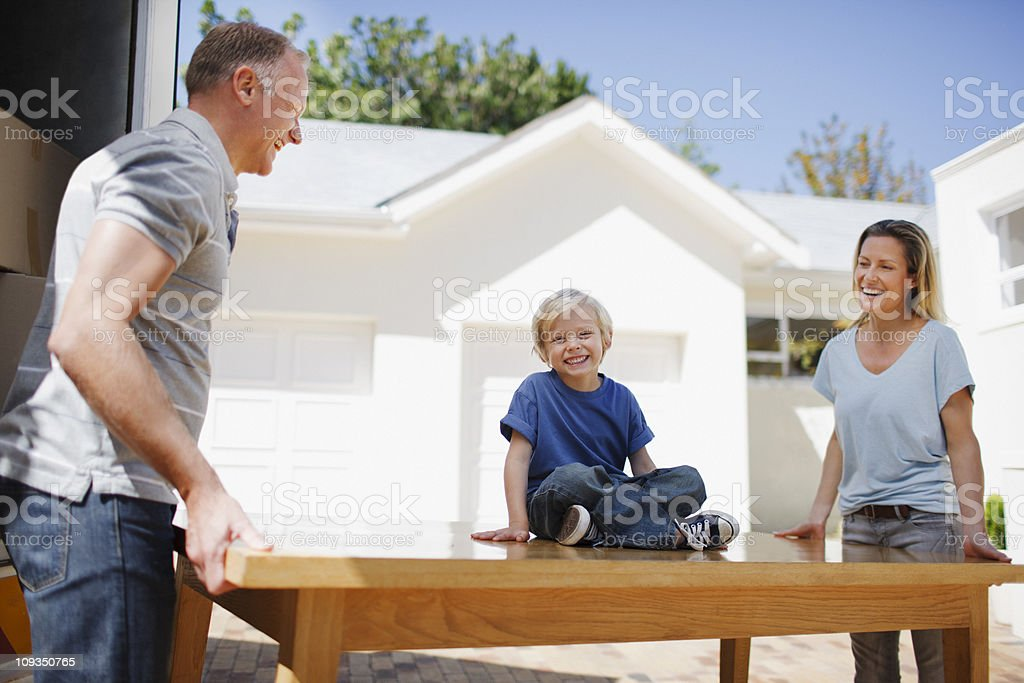 Parents and son moving table from moving van into house royalty-free stock photo