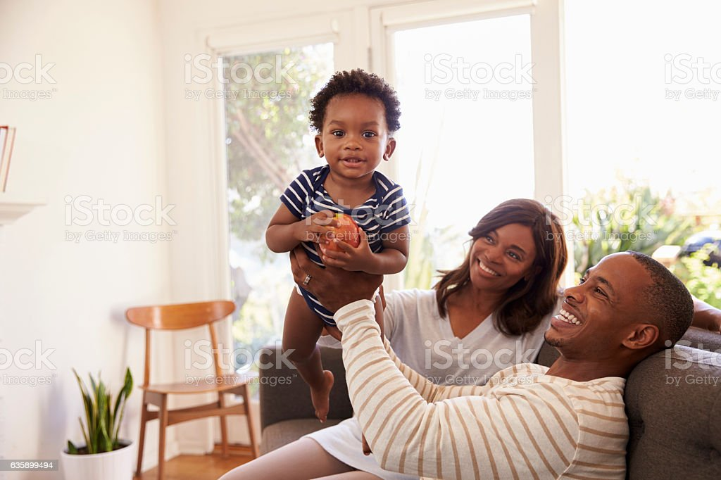 Parents And Son Playing Game On Sofa At Home stock photo