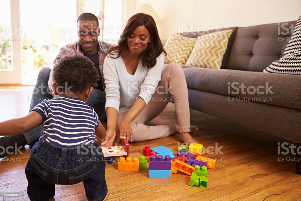 Parents And Son Playing With Toys On Floor At Home stock photo