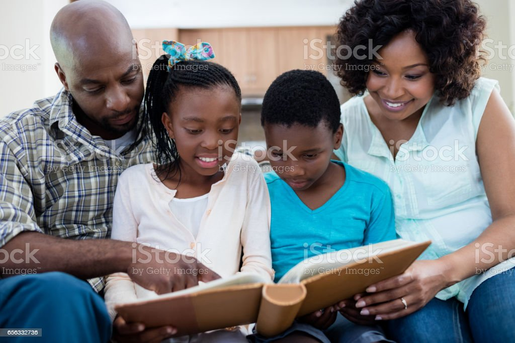 Parents and their children looking at photo album in living room stock photo