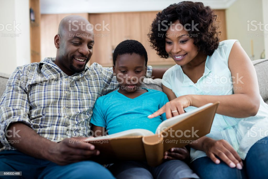 Parents and their son looking at photo album in living room stock photo