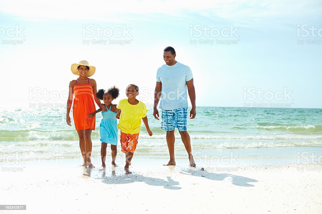 Parents and their two children on the beach stock photo