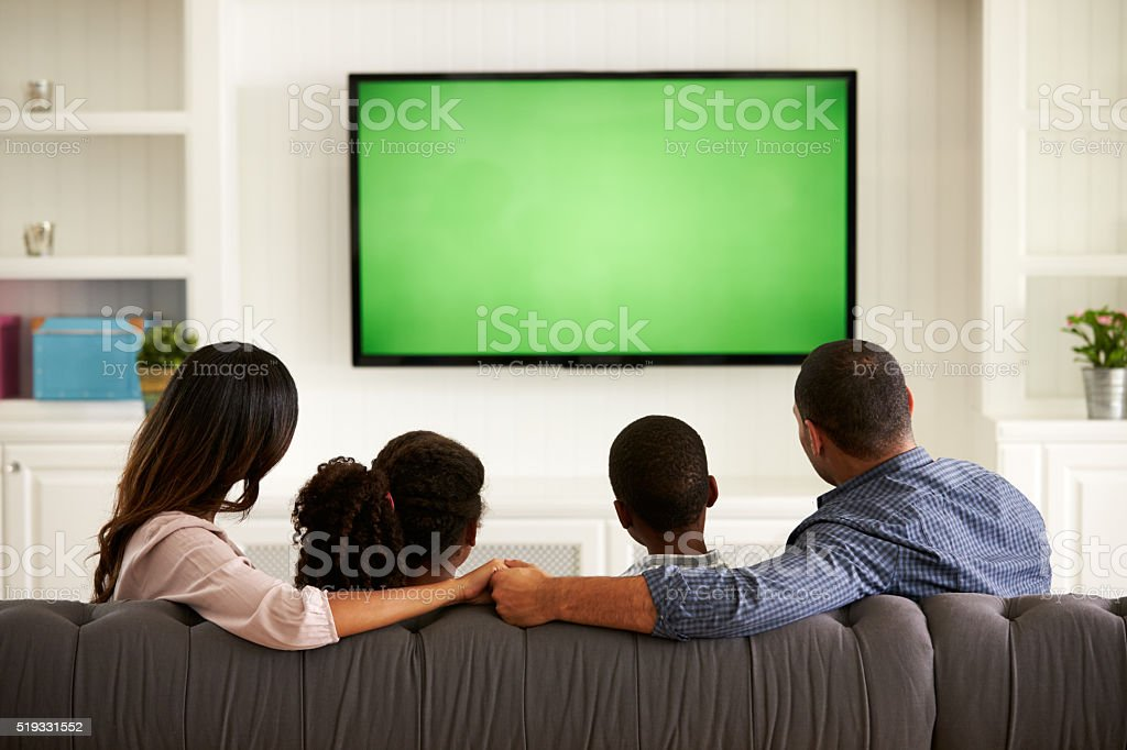 Parents and their two children watching TV together at home stock photo