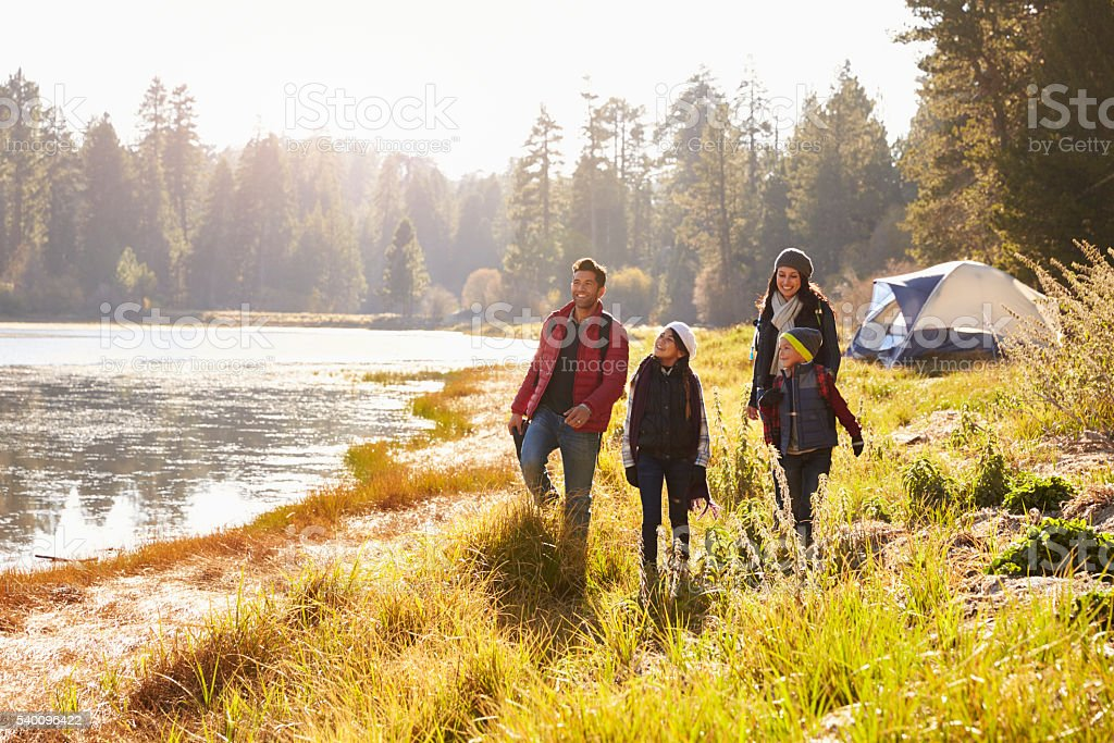 Parents and two children on camping trip walking near royalty-free stock photo
