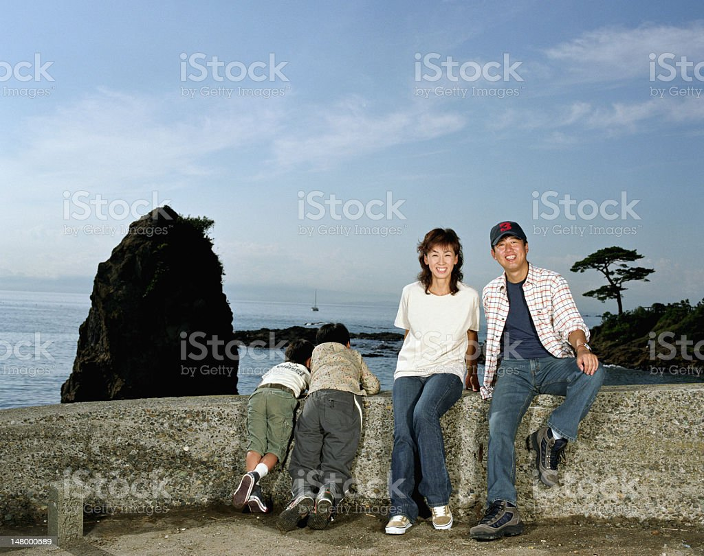 Parents and two sons (5-10) on rock wall beside sea royalty-free stock photo