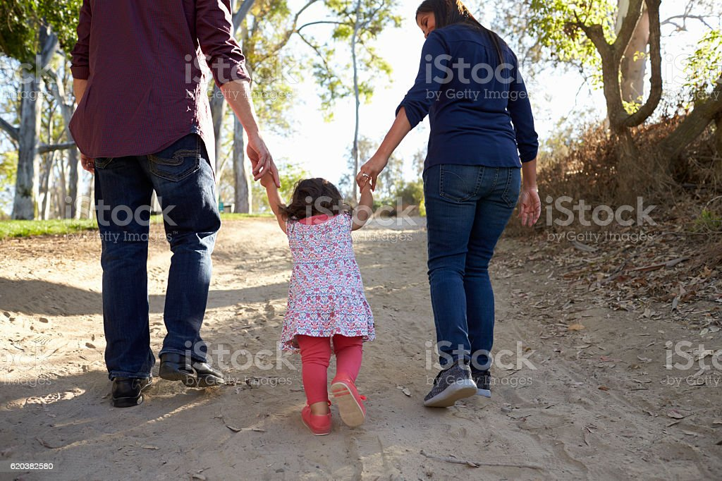 Parents and young daughter walk hand in hand on a stock photo