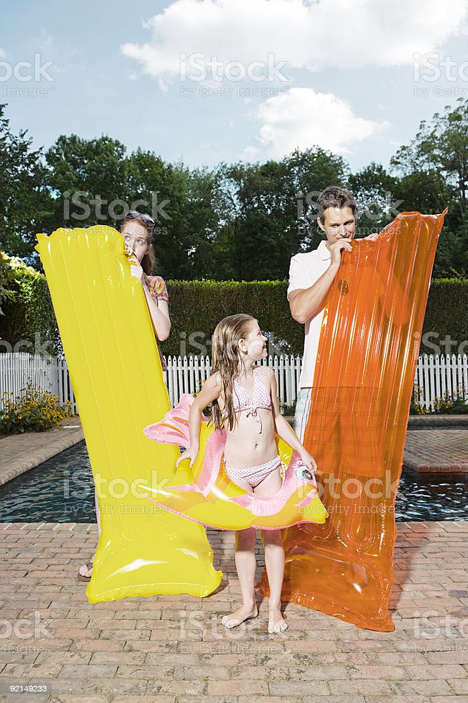 Parents ands daughter inflating air mattresses royalty-free stock photo