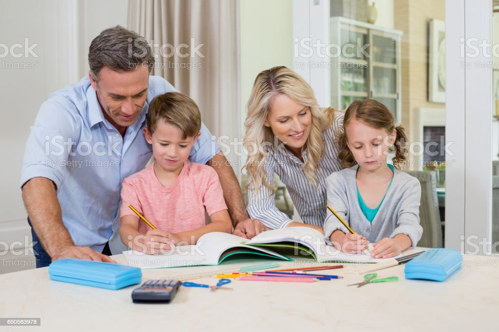 Parents assisting children doing homework stock photo