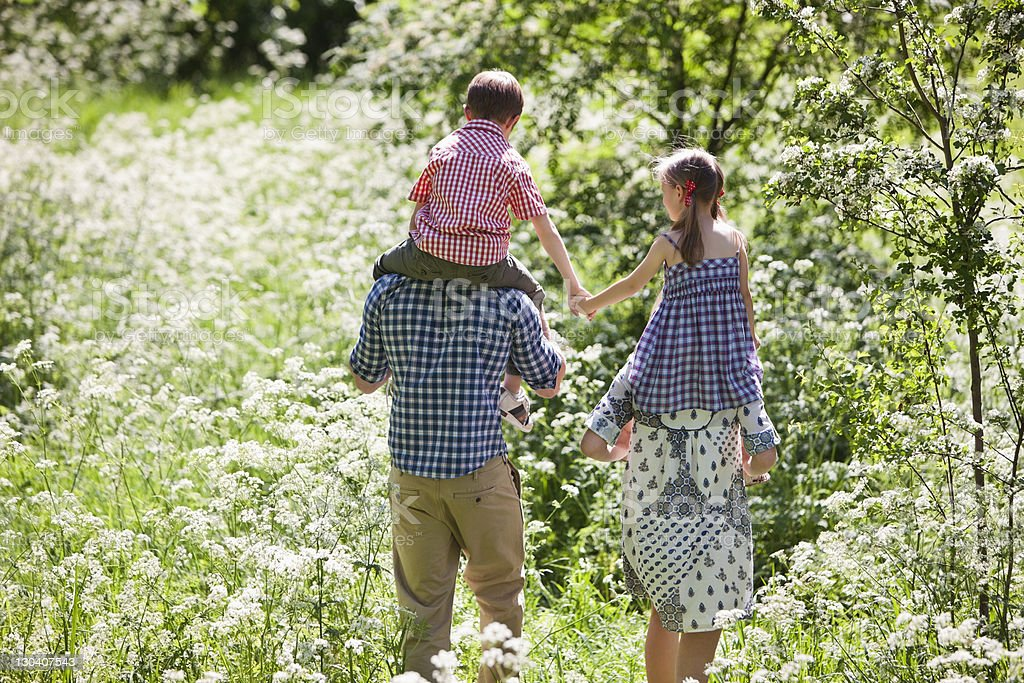 Parents carrying children on their shoulders outdoors royalty-free stock photo