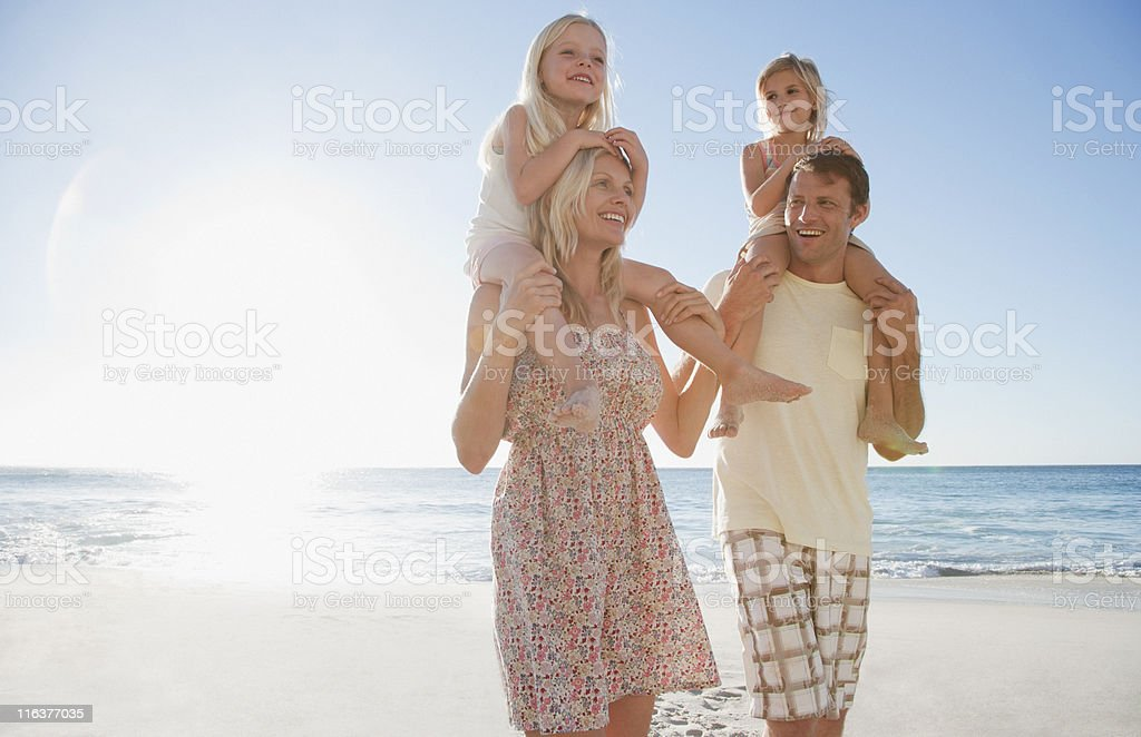 Parents carrying daughters on shoulders on beach royalty-free stock photo