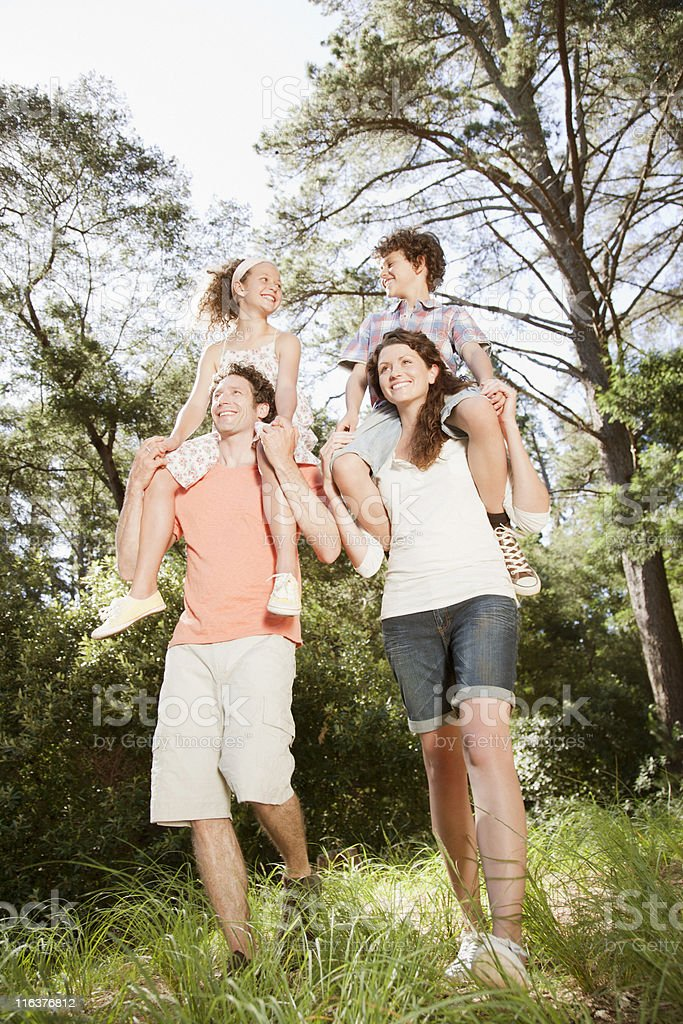 Parents carrying kids on shoulders in woods royalty-free stock photo
