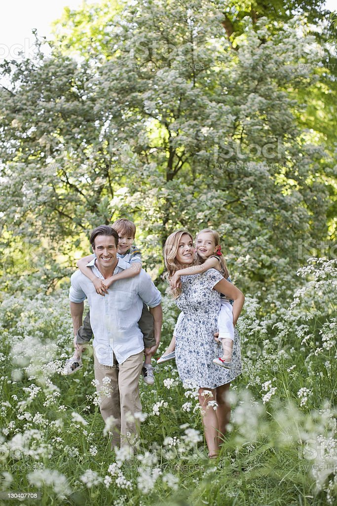 Parents carrying their children piggyback outdoors royalty-free stock photo