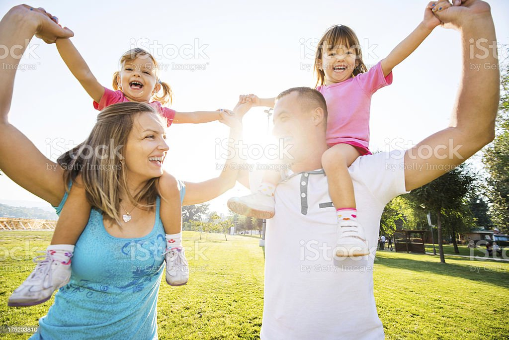 Parents carrying their daughters on the shoulders. royalty-free stock photo