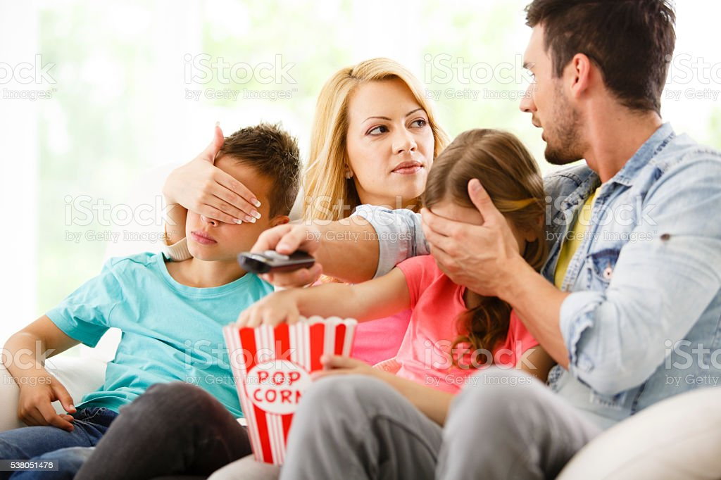 Parents cover their children's eyes while watching TV stock photo
