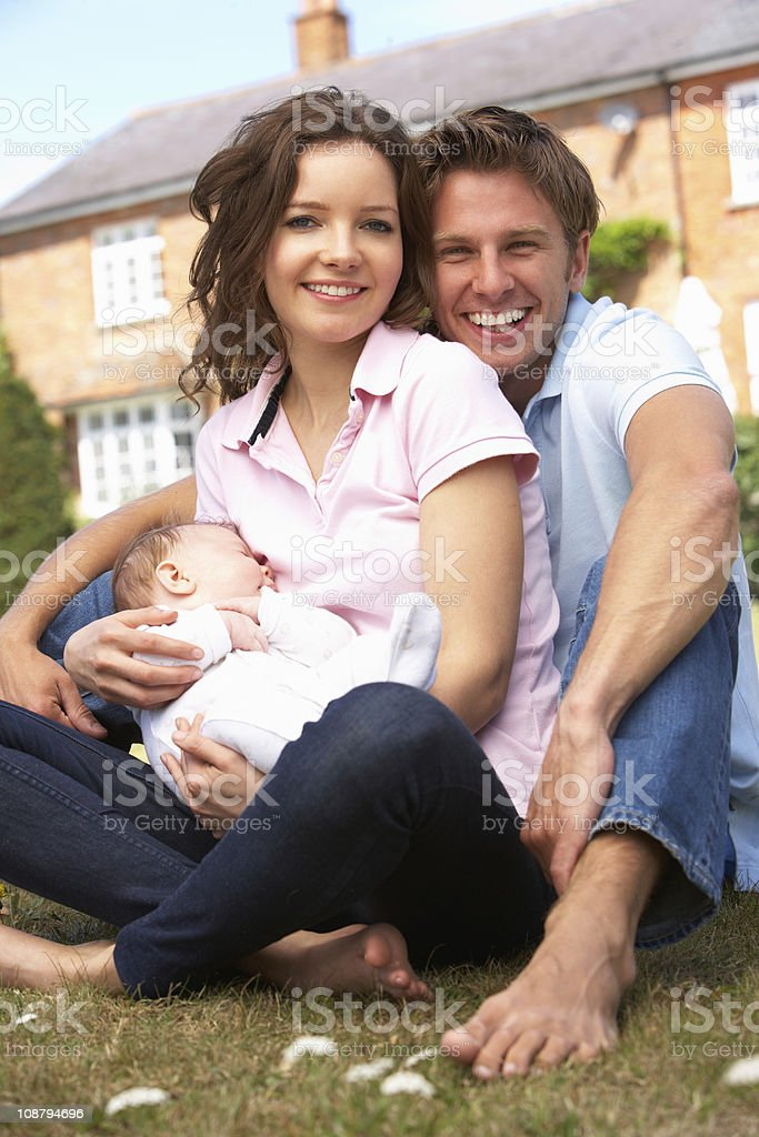 Parents Cuddling Newborn Baby Boy Outdoors At Home royalty-free stock photo