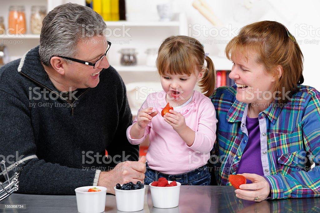 Parents Encouraging Toddler To Eat Fruit stock photo