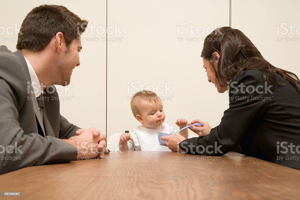 Parents feeding baby in board room royalty-free stock photo