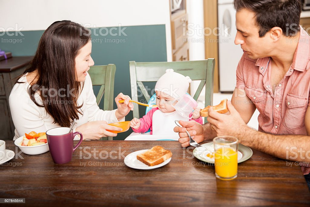 Parents feeding their baby at home stock photo