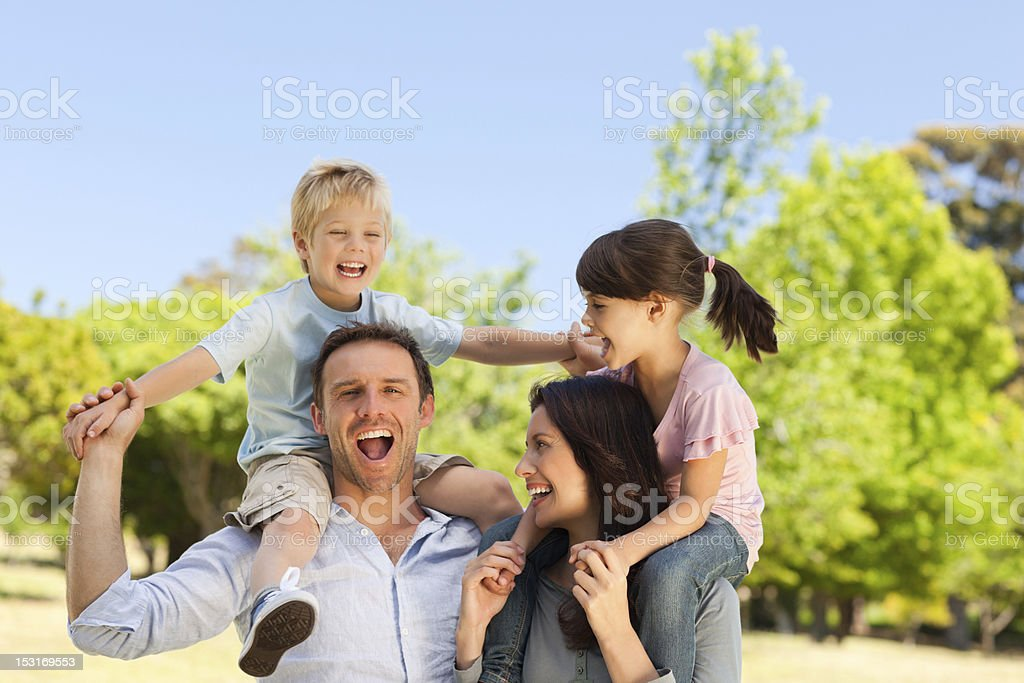 Parents giving children a piggyback royalty-free stock photo