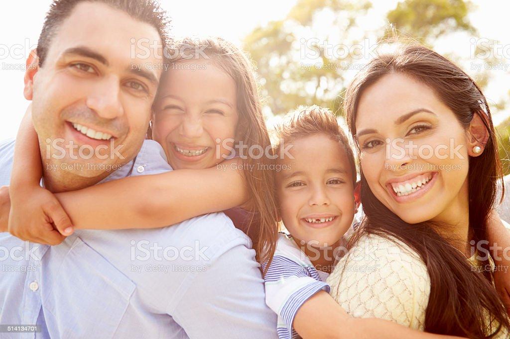 Parents Giving Children Piggyback Ride In Garden stock photo