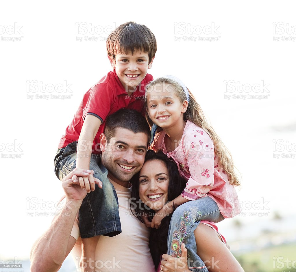 Parents giving children piggyback rides stock photo