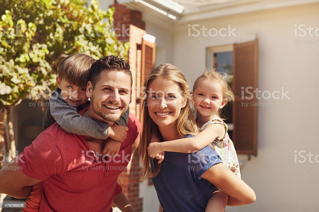 Parents giving piggyback ride to their children stock photo