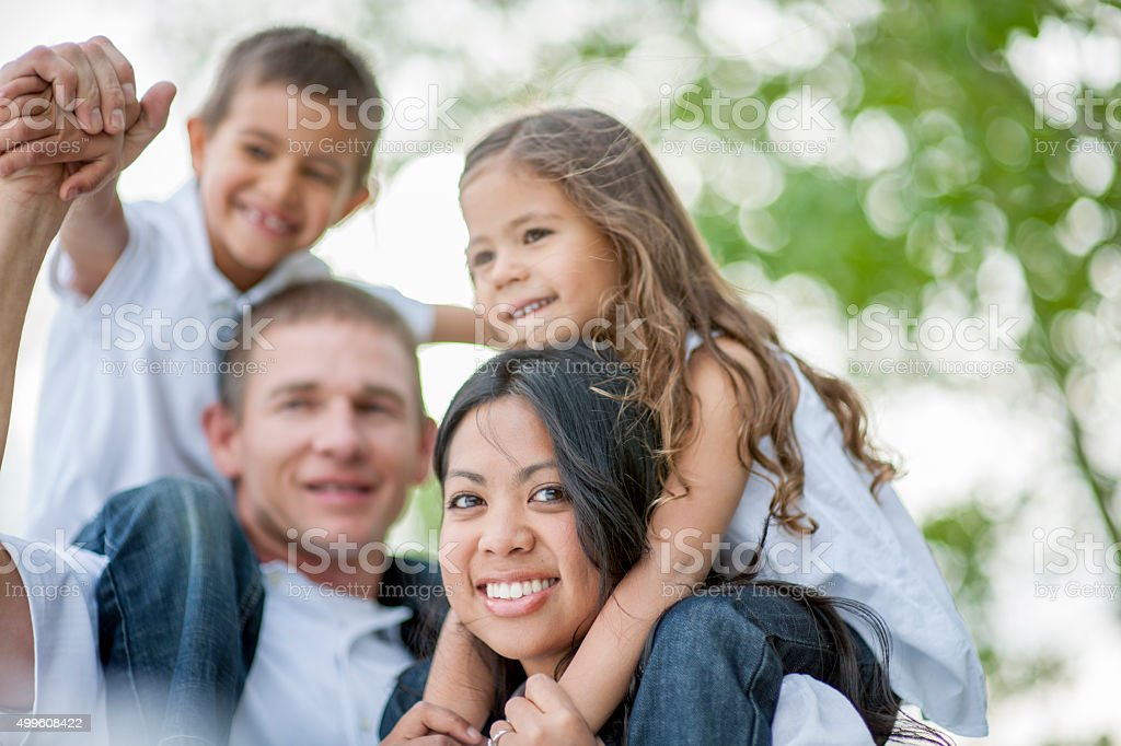 Parents Giving Their Kids a Ride on Their Shoulders stock photo