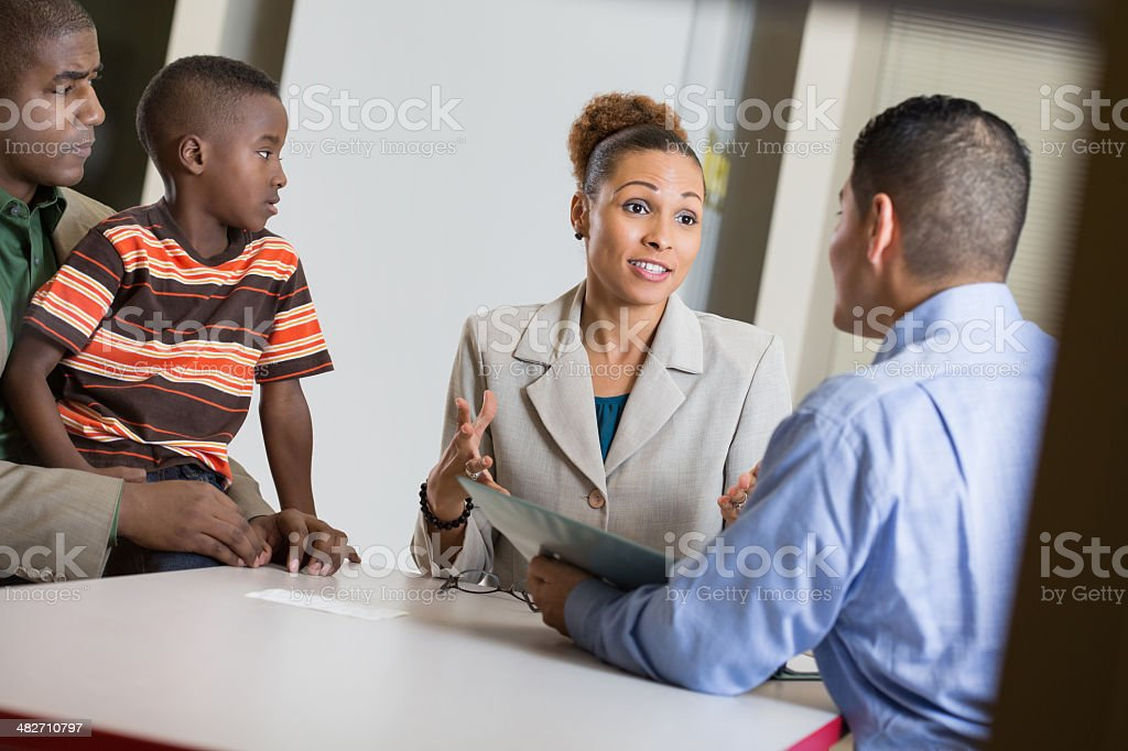 Parents having meeting with teacher at young son's school stock photo