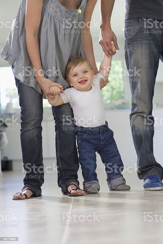 Parents help baby's first steps walking royalty-free stock photo