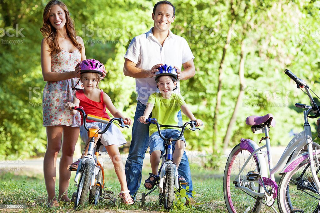 Parents Helping Children With Cycling Helmets. royalty-free stock photo